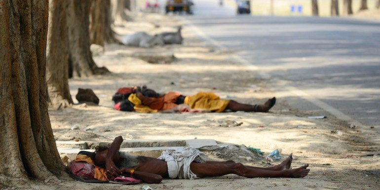 Indian homeless men rest under trees on a hot summer day in Allahabad on May 13, 2015.  AFP PHOTO/ SANJAY KANOJIA        (Photo credit should read Sanjay Kanojia/AFP/Getty Images)