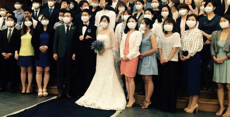 TOPSHOTS This handout photo taken on June 6, 2015 in Seoul and released by wedding planner 'Sewing for the Soil' shows a young South Korean couple (C) and dozens of guests standing together for a group photo -- almost all of their faces shielded by white masks.  The young South Korean couple became an unexpected symbol of the MERS health scare sweeping the nation after a different photo of the same group showing the couple and guests jokingly posed wearing surgical masks went viral.   AFP PHOTO / Sewing for the Soil       ----- EDITORS NOTE -----   RESTRICTED TO EDITORIAL USE   MANDATORY CREDIT